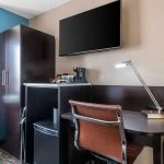 work desk with rolling chair and TV mounted on wall at Clarion Hotel Auburn-Kent-Seattle