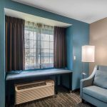 hotel room seating area with blue chair next to window at Clarion Hotel Auburn-Kent-Seattle