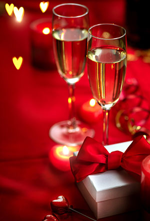 Table setting with Champagne in two glasses, candles and gift box over holiday red background with hearts